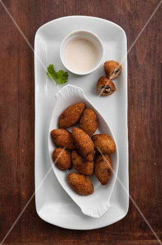 Kibbeh (North African bulgur dumplings) filled with nuts, with a tahini dressing