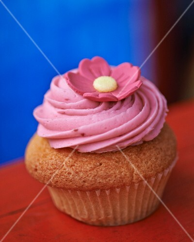 A cupcake topped with pink icing and a flower decoration
