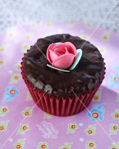 A chocolate cupcake with a sugar flower