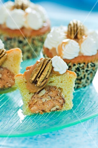 Cupcakes filled with nuts and topped with toffee, pecans and whipped cream
