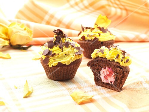 Chocolate cupcakes with strawberry cream filling, topped with lemon icing