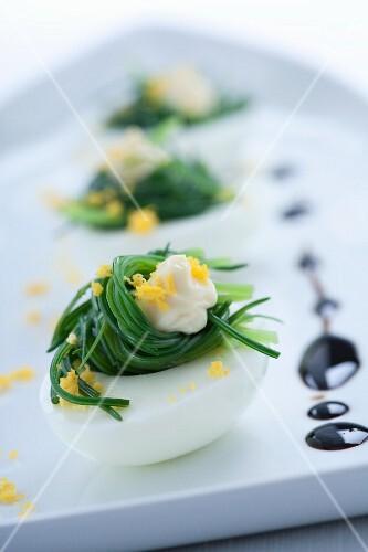 Mit Mönchsbart gefüllte und mit Eidotter bestreute Eier; dazu Balsamessig
