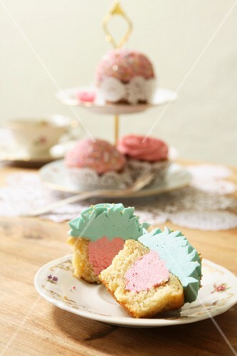 A cupcake with a strawberry buttercream filling and topped with turquoise icing, with a tiered cake stand in the background