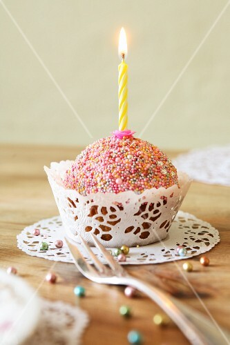A cupcake decorated with colourful sugar sprinkles and a candle