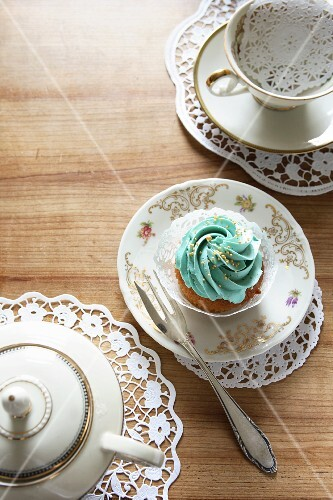 A teaset and a cupcake topped with turquoise icing