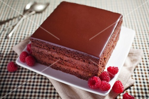 A slice of chocolate cake with fresh raspberries