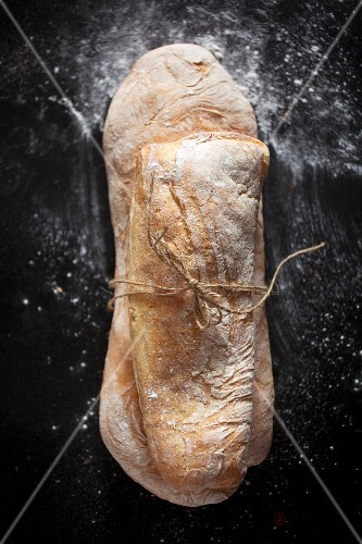 Two ciabatta rolls tied together with string (view from above)