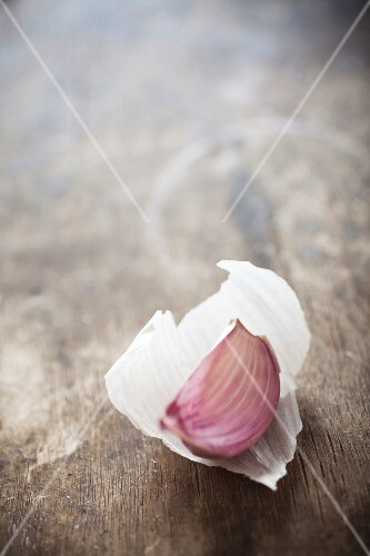 A clove of garlic on a wooden surface