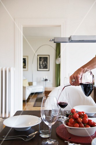 A woman pouring red wine into a glass on a table laid for a meal