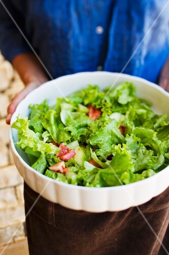 A woman holding a bowl of salad (lettuce with cucumbers, tomatoes and vinaigrette)