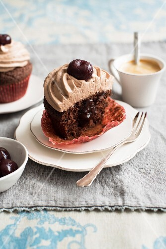 Half of a cherry cupcake with chocolate sauce
