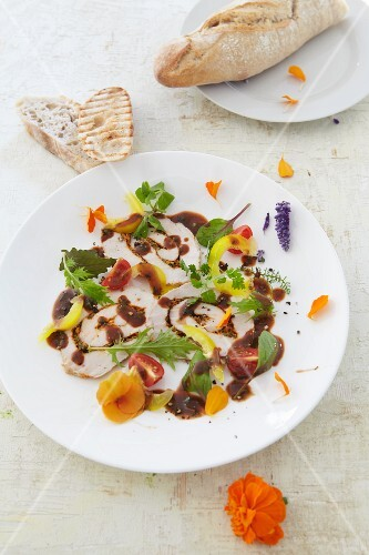 Carpaccio of suckling pig with edible flowers and balsamic vinegar