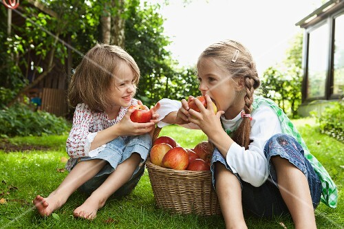 Two girls eating apples in the garden