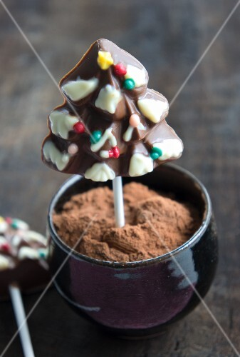 A chocolate Christmas tree on a stick in a bowl of cocoa powder