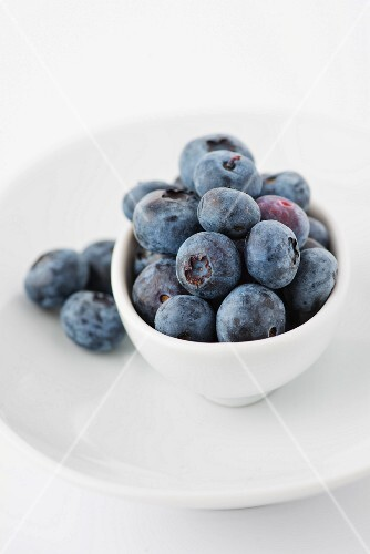 Blueberries in a white dish and on a plate
