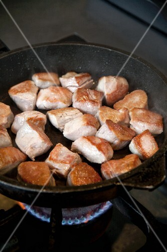 Chunks of pork being fried in an iron pan