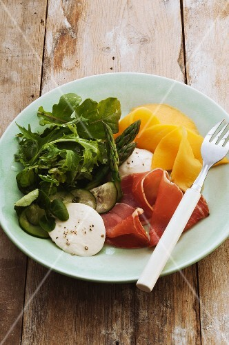 Prosciutto with mango, mozzarella and salad leaves