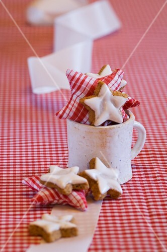 Star-shaped cinnamon biscuits and fabric stars in a mug
