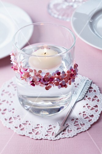 Floating candle in glass decorated with confetti on doily