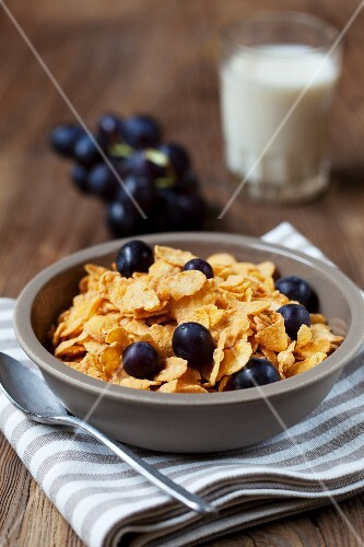 Cornflakes with red grapes, with a glass of milk in the background