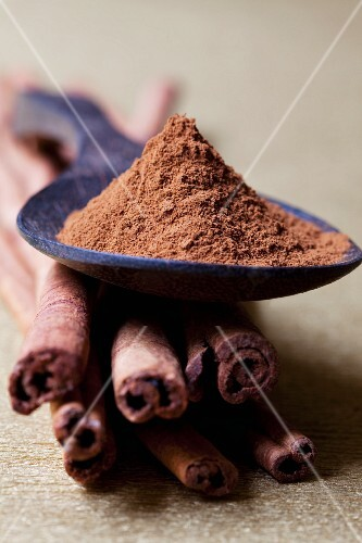 Cinnamon sticks with a spoon full of ground cinnamon on top