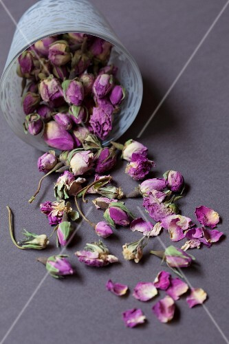 An overturned glass of dried rose buds