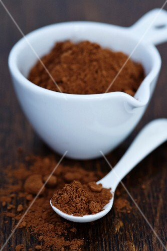 Cocoa powder in a small bowl and on a spoon