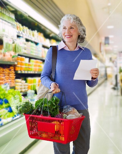 USA, New Jersey, Jersey City, Senior woman carrying shopping basket in supermarket