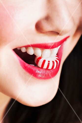 Close up of woman's mouths with red lipstick holding striped candy
