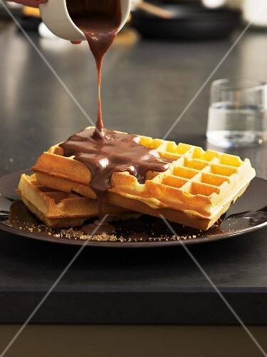 Nougat sauce being poured over waffles