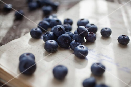 Blueberries on a sheet of paper covered in writing