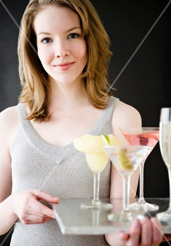Woman holding tray of cocktails