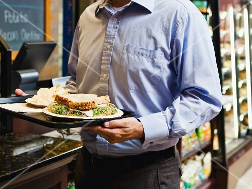 Man carrying sandwich on tray