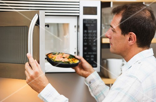 Man inserting meal in microwave oven