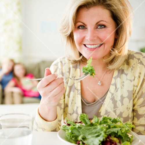 A blonde woman eating salad
