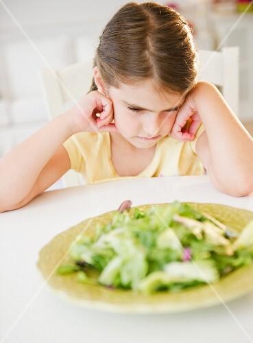 Verärgertes Mädchen sitzt vor Salatteller