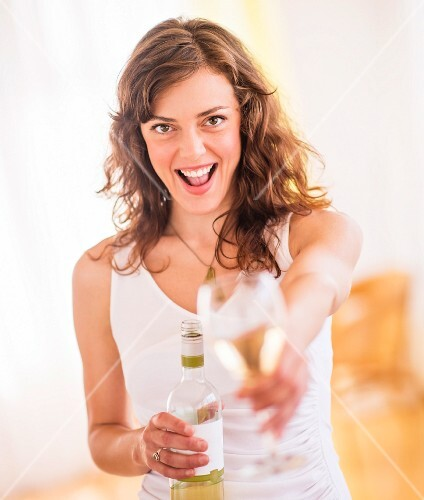 Woman holding wine bottle and glass