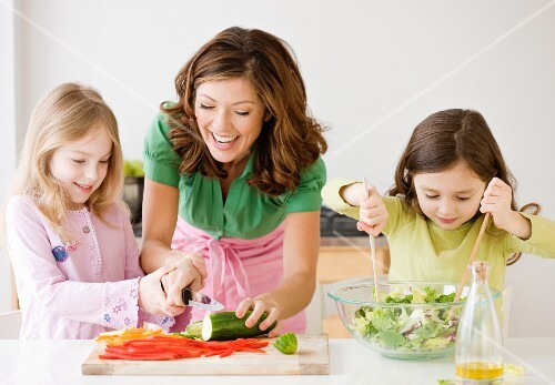 Mother and daughters preparing food