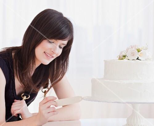 Young woman observing wedding cake, studio shot