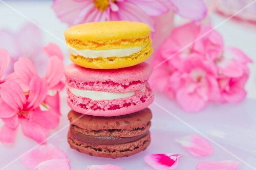Stacked macarons (chocolate, strawberry, lemon) in front of pink flowers
