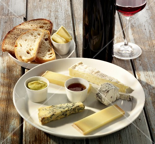 A plate of cheese with mustard, bread, butter and wine