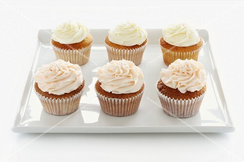 Six buttercream cupcakes on a square tray