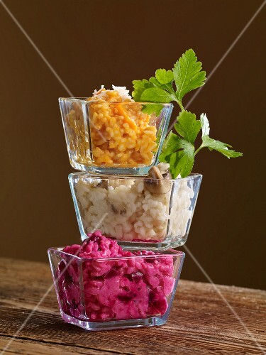 Three types of risotto in glass bowls stacked on top of one another
