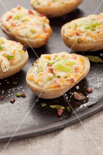 Stuffed baked potato halves with spring onions