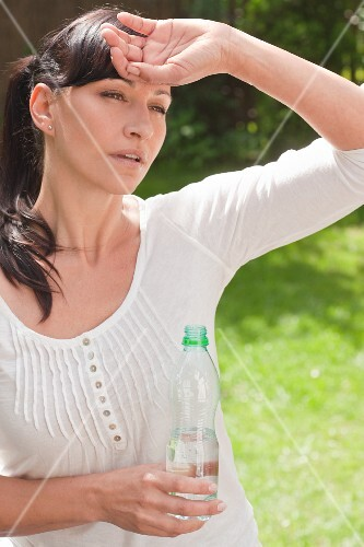 Woman in the hot summer sun with a water bottle in the garden