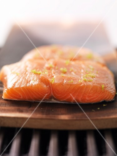 Raw salmon filled on cedar wood on the barbecue