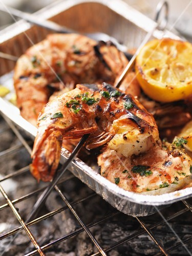 Barbecued king prawns in an aluminium tray on the barbecue