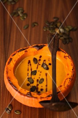 Pumpkin soup in a scooped out pumpkin shell with pumpkin seeds