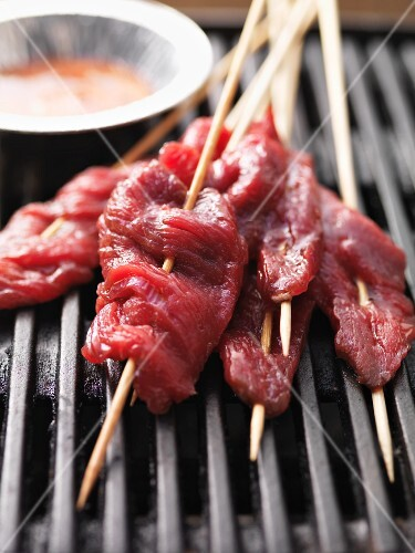 Raw satay skewers on the barbecue