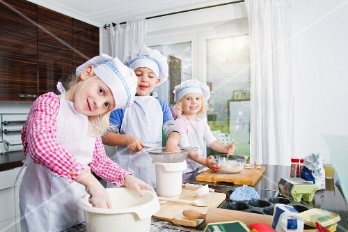 Germany, Girls and boy making dough in kitchen